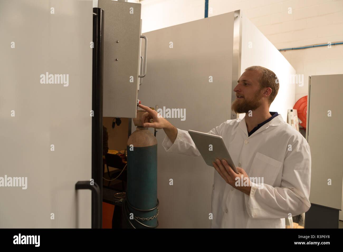 Robotics engineer controlling control panel - Stock Image