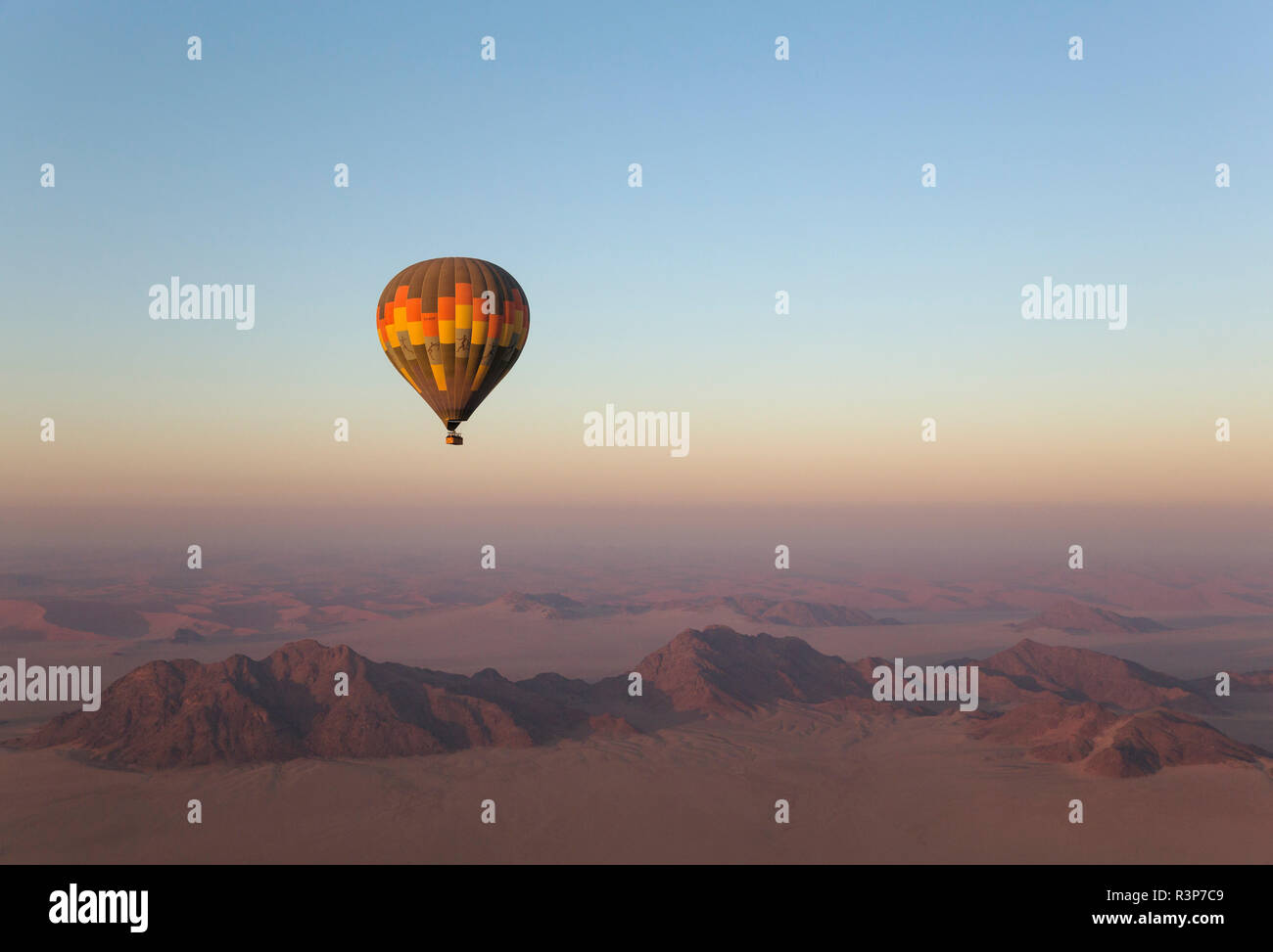 The hot-air balloon above an arid plain and isolated mountain ridges at the edge of the Namib Desert. Aerial view from a second balloon. NamibRand Nature Reserve, Namibia. Stock Photo