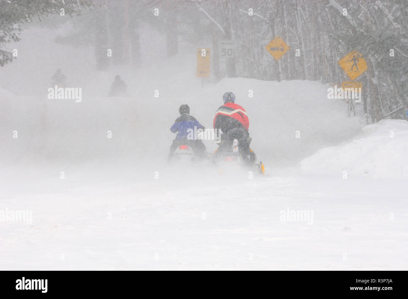 Canada, Ontario, Dorset. Snowmobiles on country road. - Stock Image