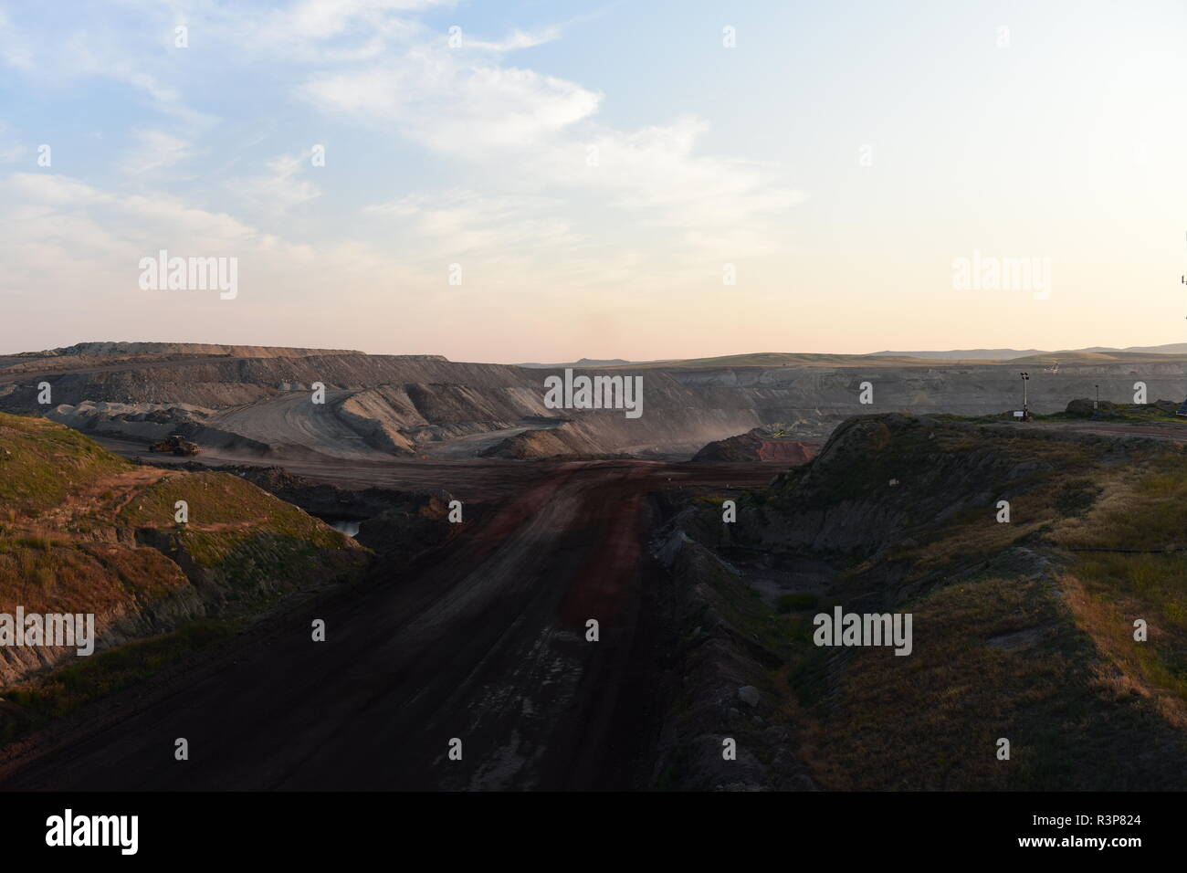 Lone vehicle driving through an open pit coal mine in the Powder River Basin, Wyoming / USA. Stock Photo