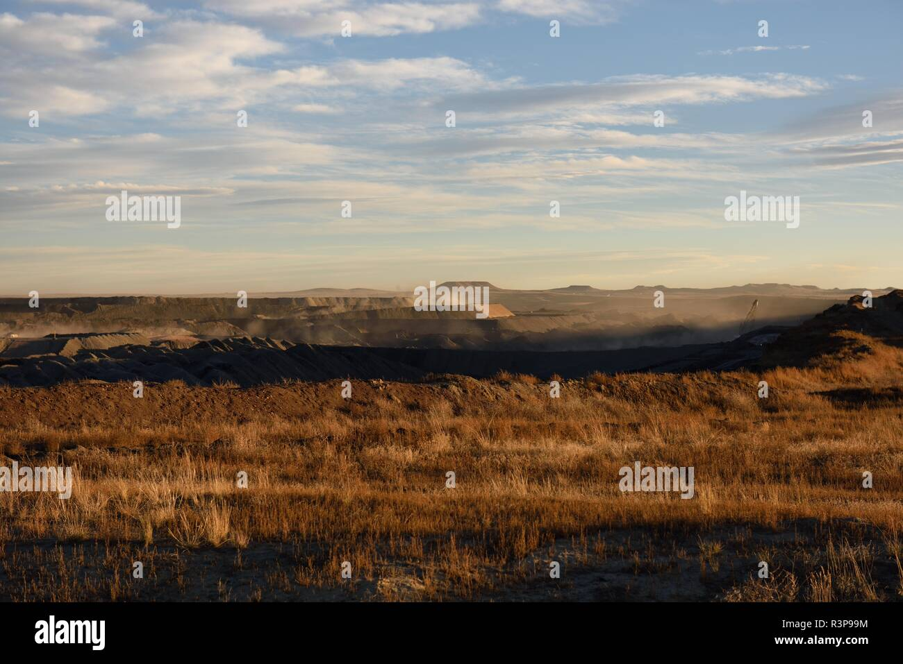Dust clouds rising from inside the landscape of an open pit coal mine in the Powder River Basin in Wyoming, USA. Stock Photo