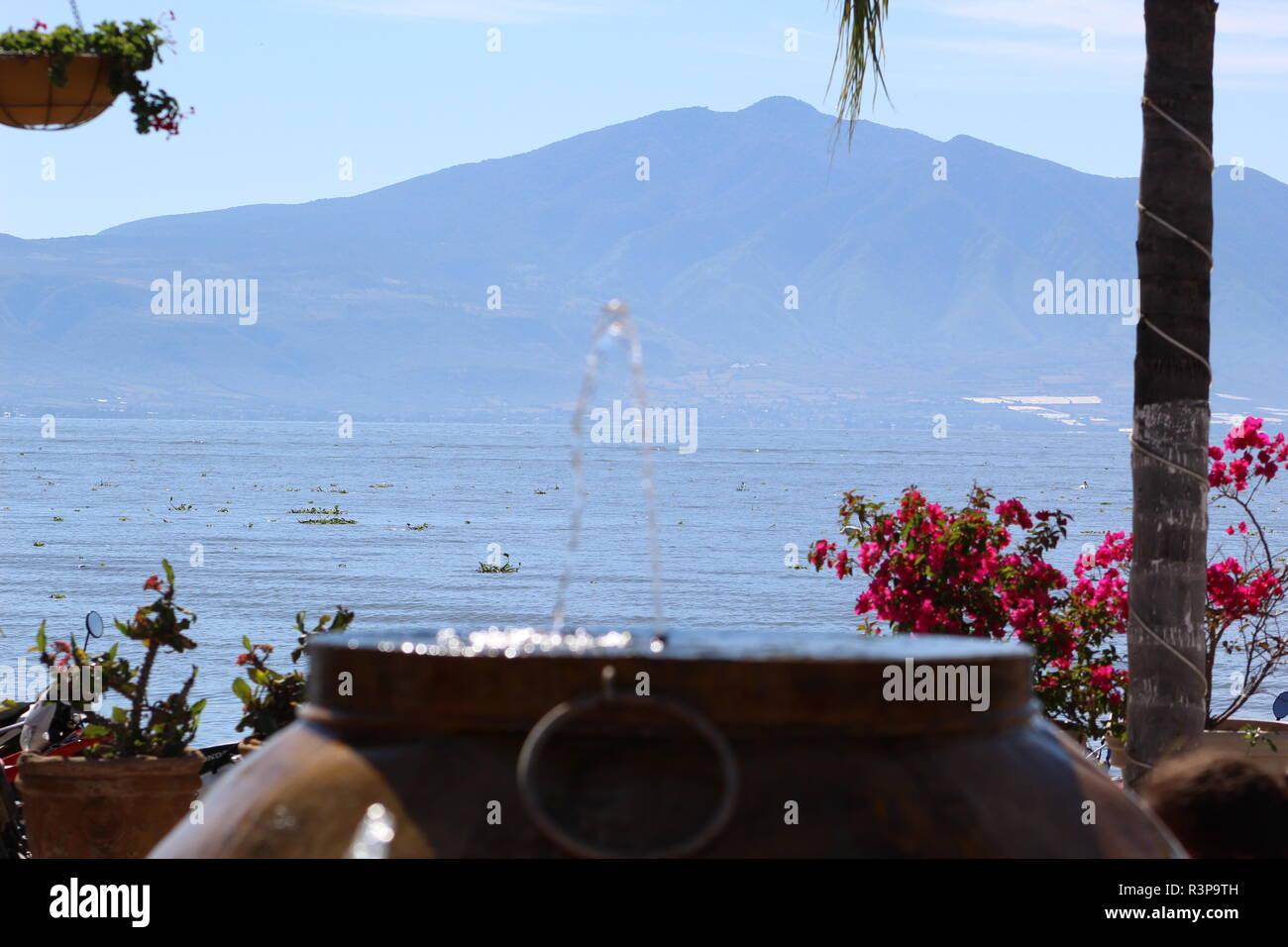Fuente de vasija en Chapala, Jalisco, Mexico foto tomada a medio dia  en la que aparece en primer plano la fuente, en segundo plano unas flores - Stock Image