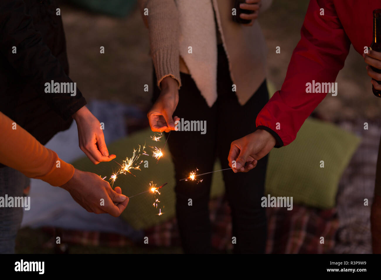 Group of friends having fun with sparklers - Stock Image