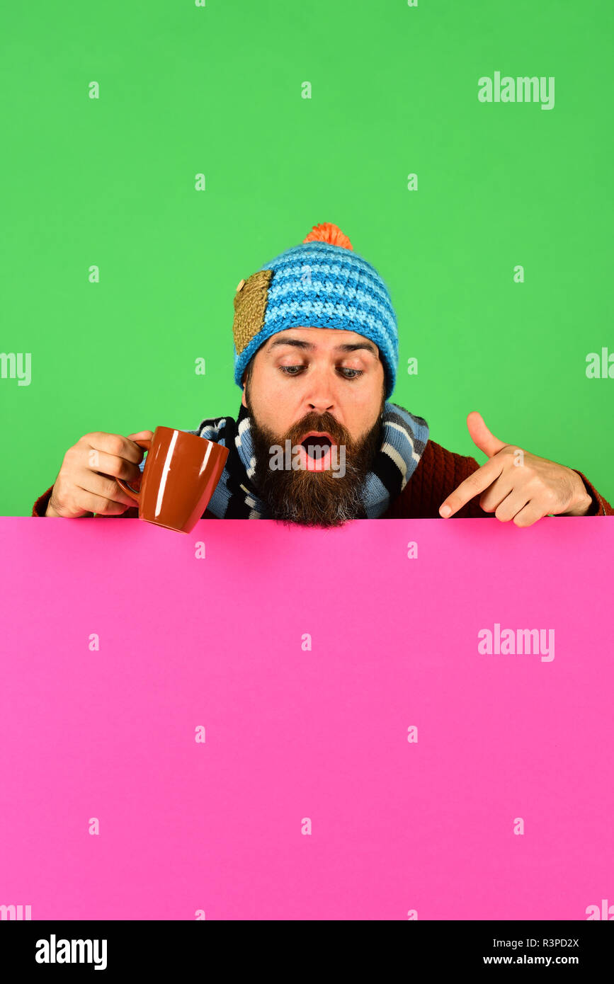 October beverage idea. Man in warm hat holds brown cup on green and pink background, copy space. Autumn and hot drink season concept. Hipster and surp - Stock Image