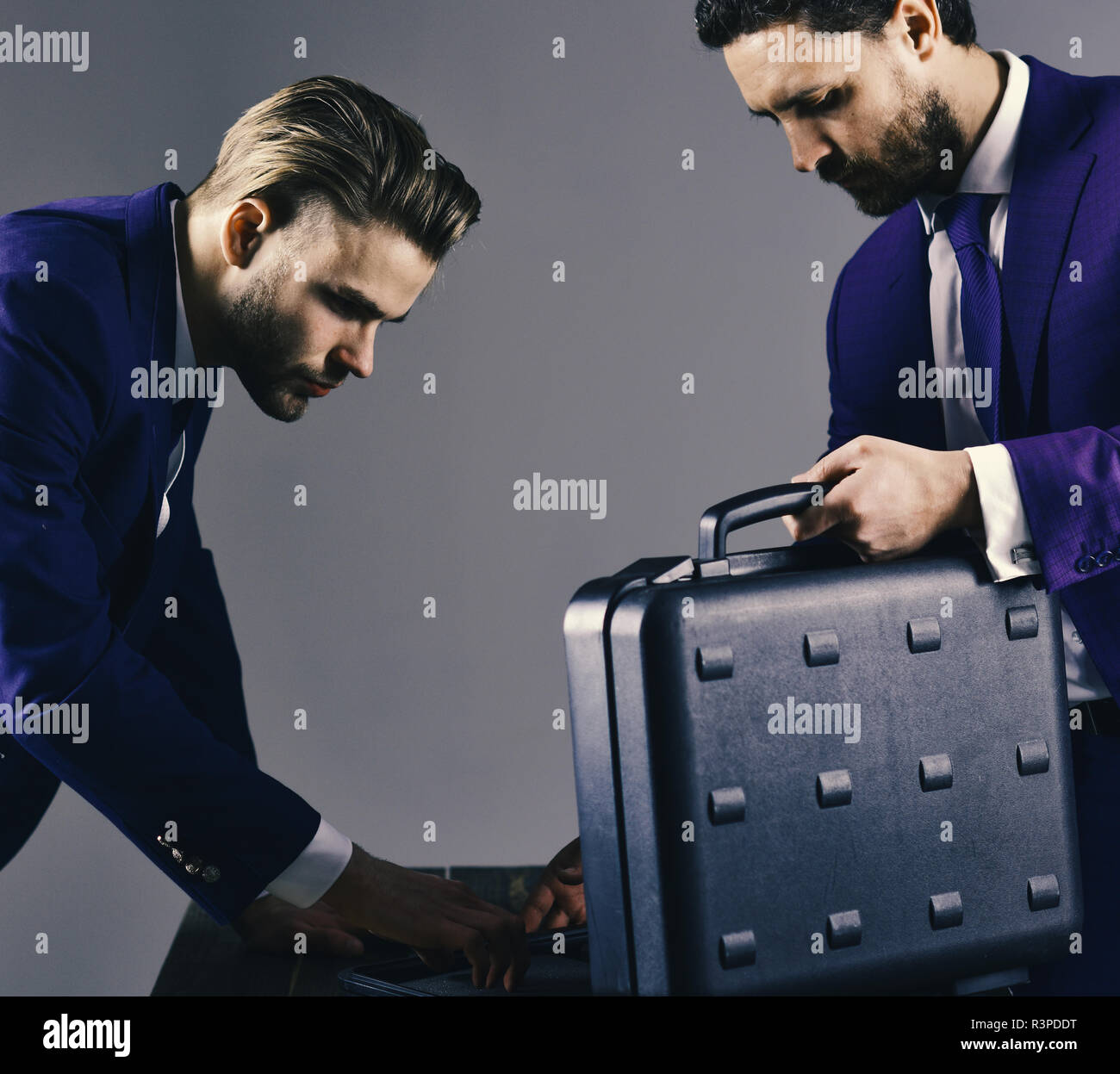 Businessmen offer illegal transaction or bribe. Business exchange concept. Businessmen look into opened briefcase on dark background. Men in suit or b - Stock Image