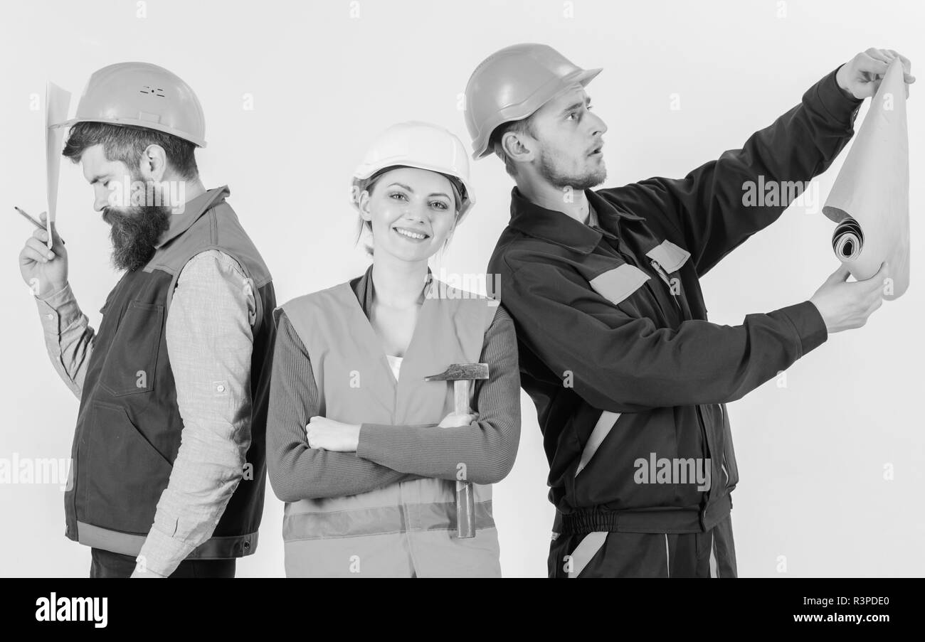 Insubordination concept. Inspector disappointed about employee, builder. Men and woman in helmets carefree with hammer and project , white background. - Stock Image