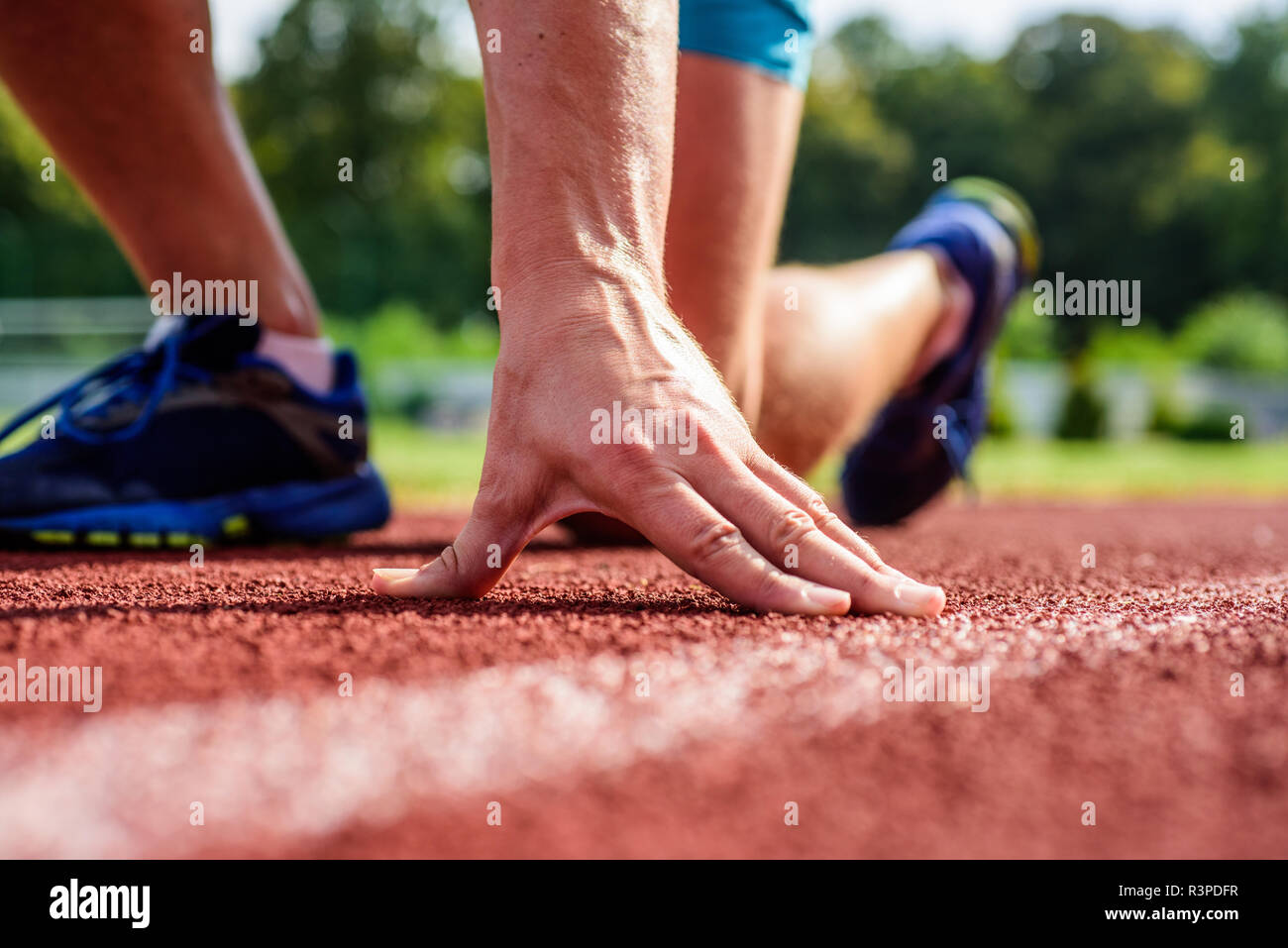 Flexibility is ability to stretch joint to limit of range movement. Joint care for runners. Ultimate remedies. Hand of sportsman on running track low  - Stock Image