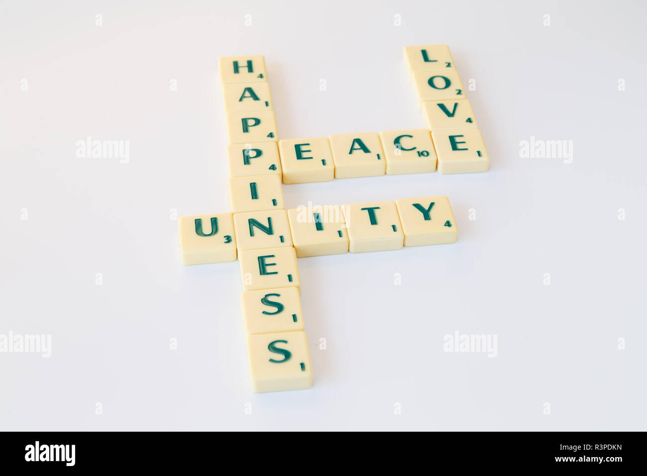 Scrabble game letter tiles with score value forming the words Peace, Love, Unity and Happiness on white background. - Stock Image