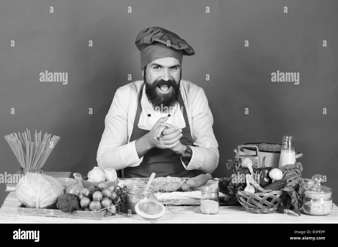 Cooking process concept. Cook with tricky face in burgundy uniform rubs hands near ingredients. Man with beard sits by countertop on green background. - Stock Image