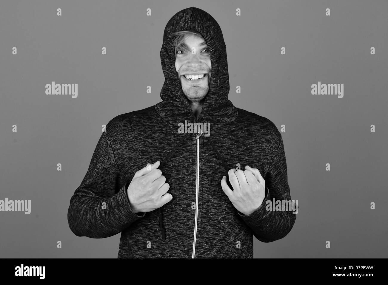 Guy with bristle in dark grey and black hoodie. Sports fashion and fun concept. Man with head covered all over with hood on purple background. Macho w - Stock Image