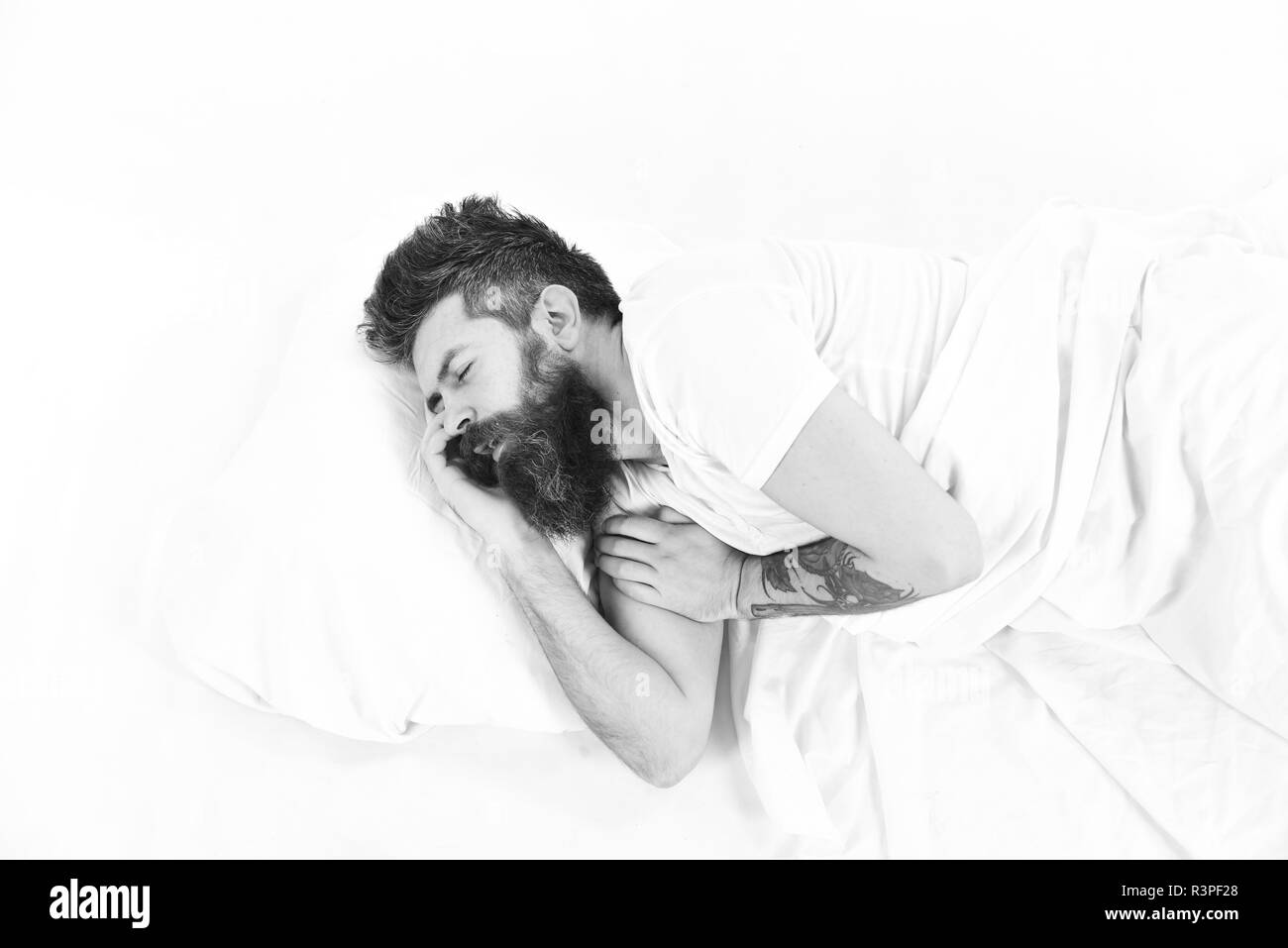 Hipster with beard fall asleep. Man with sleepy face lies on pillow. Deep sleep concept. Man with beard and mustache in deep sleep, white background.  - Stock Image