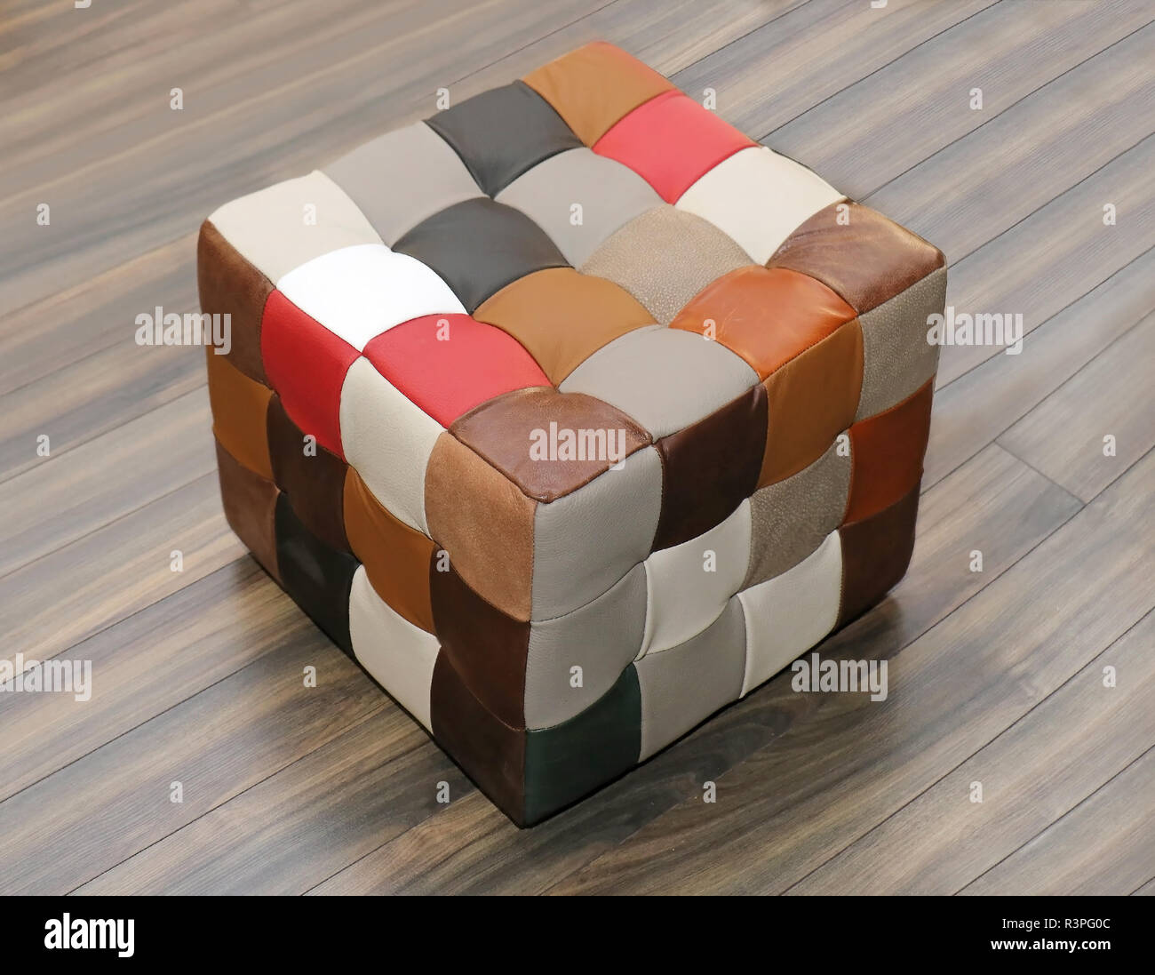 Small footstool furniture with colorful leather upholstery on wooden floor - Stock Image