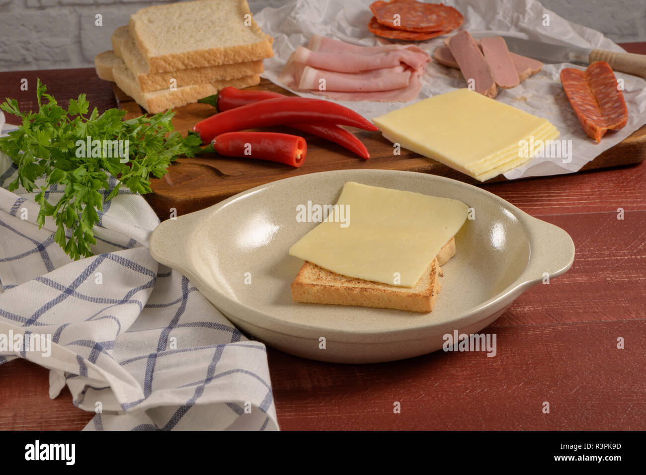 Ingredients preparations of traditional Portuguese snack food. Francesinha sandwich of bread, cheese, pork, ham, sausages. On table. Stock Photo