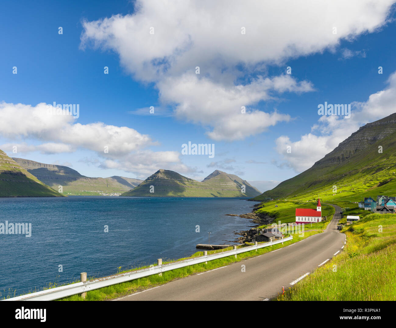 The church in village Husar on Kalsoy, in the background the island of Bordoy and Klaksvik. Faroe Islands, Denmark - Stock Image
