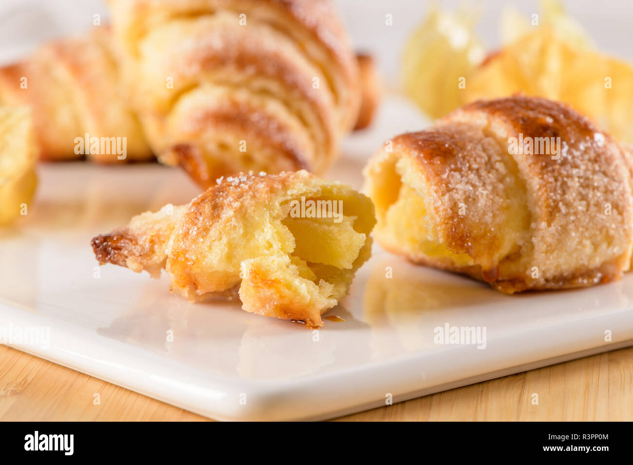 Small croissant with physalis fruits in white ceramic tray, homemade cakes on wooden table top. - Stock Image
