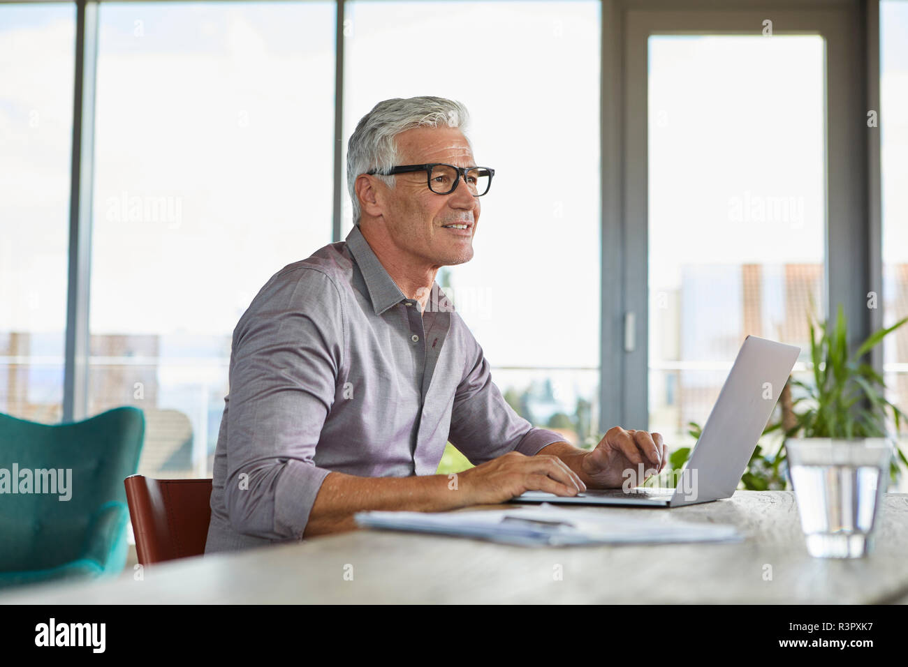 Mature man using laptop on table at home Stock Photo