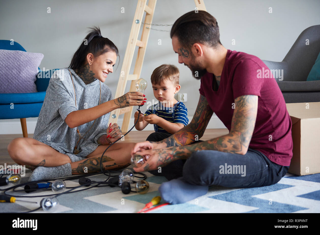 Happy modern family decorating the home for Christmas - Stock Image