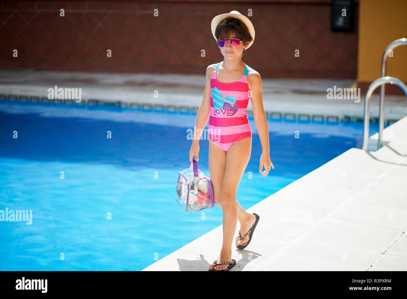 Young girl arriving at the pool in summer with bath clothes - Stock Image