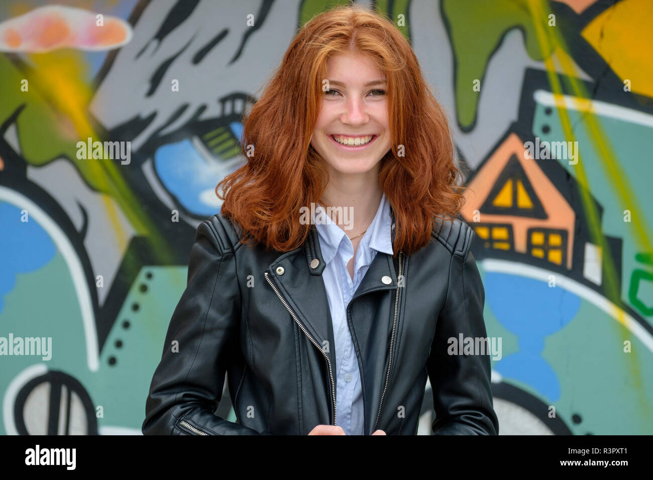 Italy, Finale Ligure, portrait of laughing redheaded teenage girl in front of  mural - Stock Image
