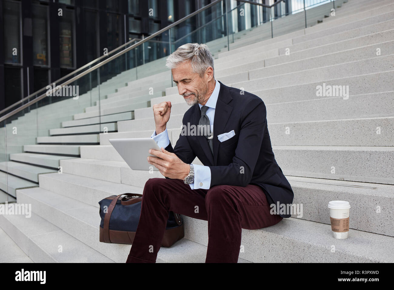 Fashionable businessman with travelling bag nd coffee to go sitting on stairs using tablet - Stock Image