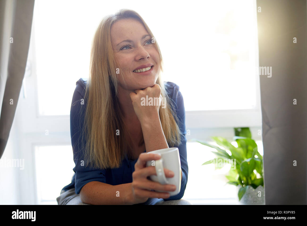 Young woman drinking coffee at home Stock Photo