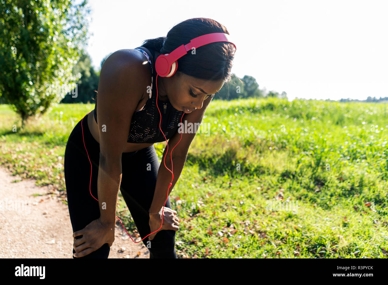 Young athlete in nature, listening music with headphones, preparing for training - Stock Image