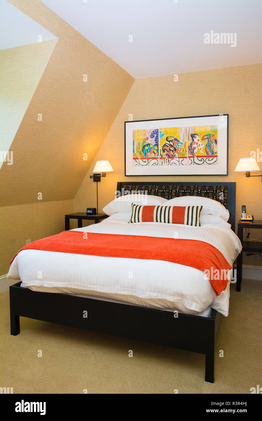 An interior shot of a hotel bedroom decorated with orange accents ...