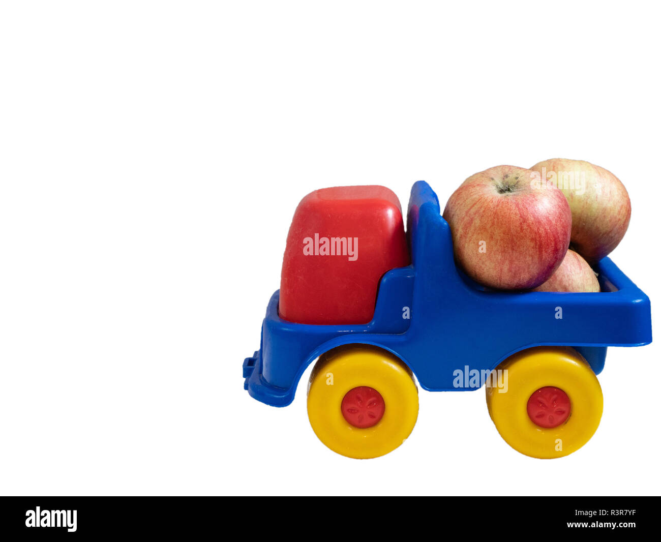side shot of small colorful toy car truck with apples fruits. organic fruits delivery. isolated on white background - Stock Image