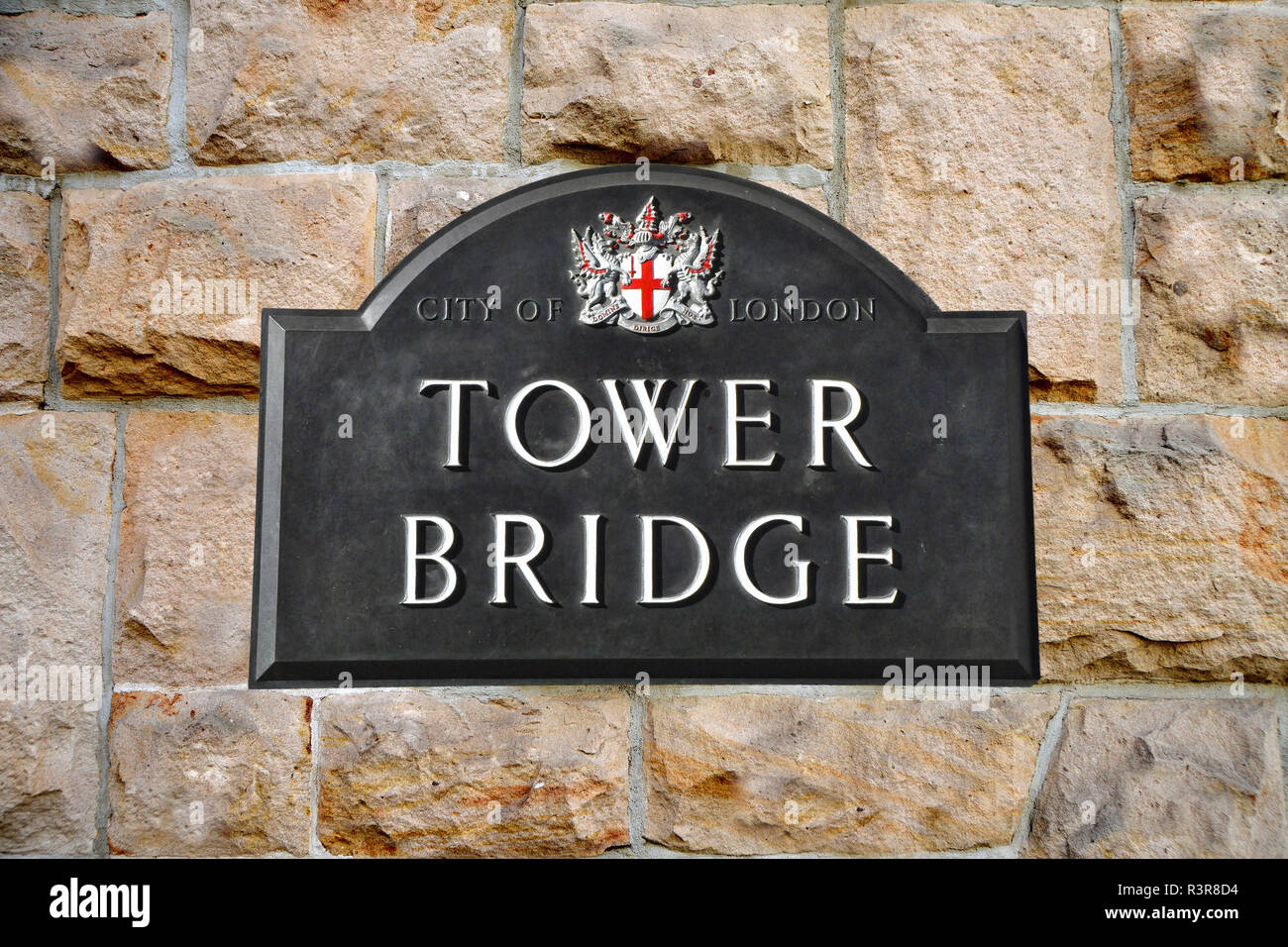 Tower Bridge sign in London in the background a sandstone wall - Stock Image