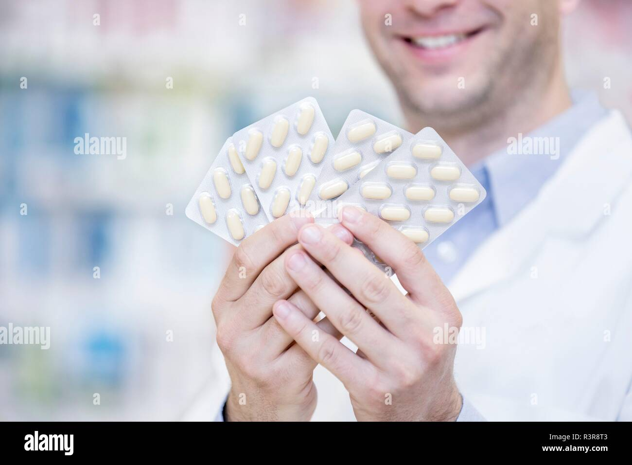 Pharmacist holding blister packs in pharmacy. - Stock Image