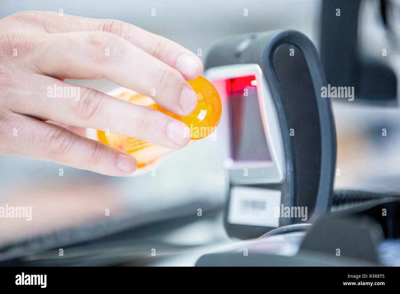 Pharmacist scanning medicine with barcode reader in pharmacy. - Stock Image