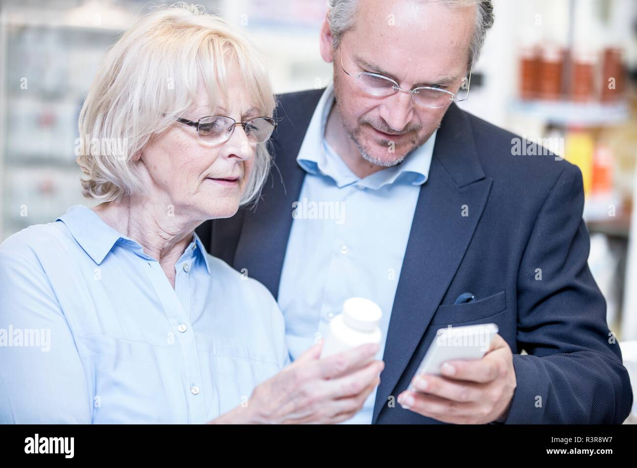 Senior couple checking medicine on mobile phone in pharmacy. - Stock Image