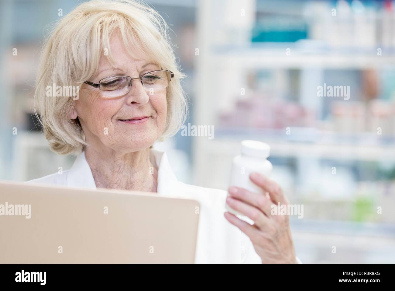 Senior female pharmacist holding laptop and reading label on pill bottle in pharmacy. - Stock Image