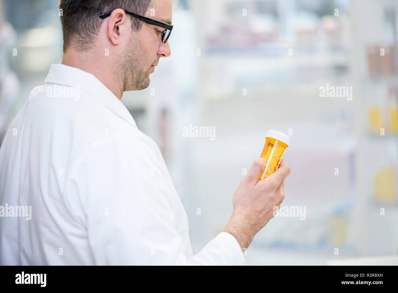 Pharmacist reading label on pill bottle in pharmacy. - Stock Image