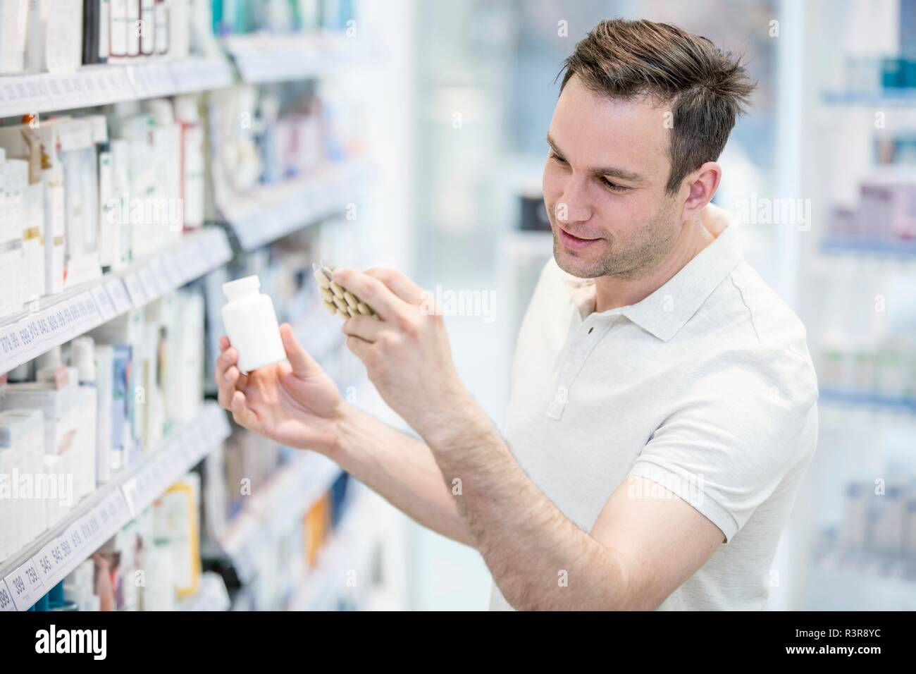 Male customer reading label on pill blister pack in pharmacy. - Stock Image
