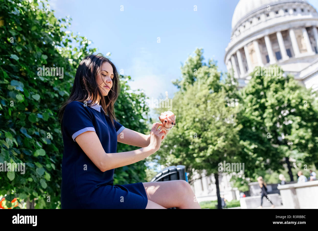 UK, London, young woman using her smartwatch near St. Paul's Cathedral Stock Photo