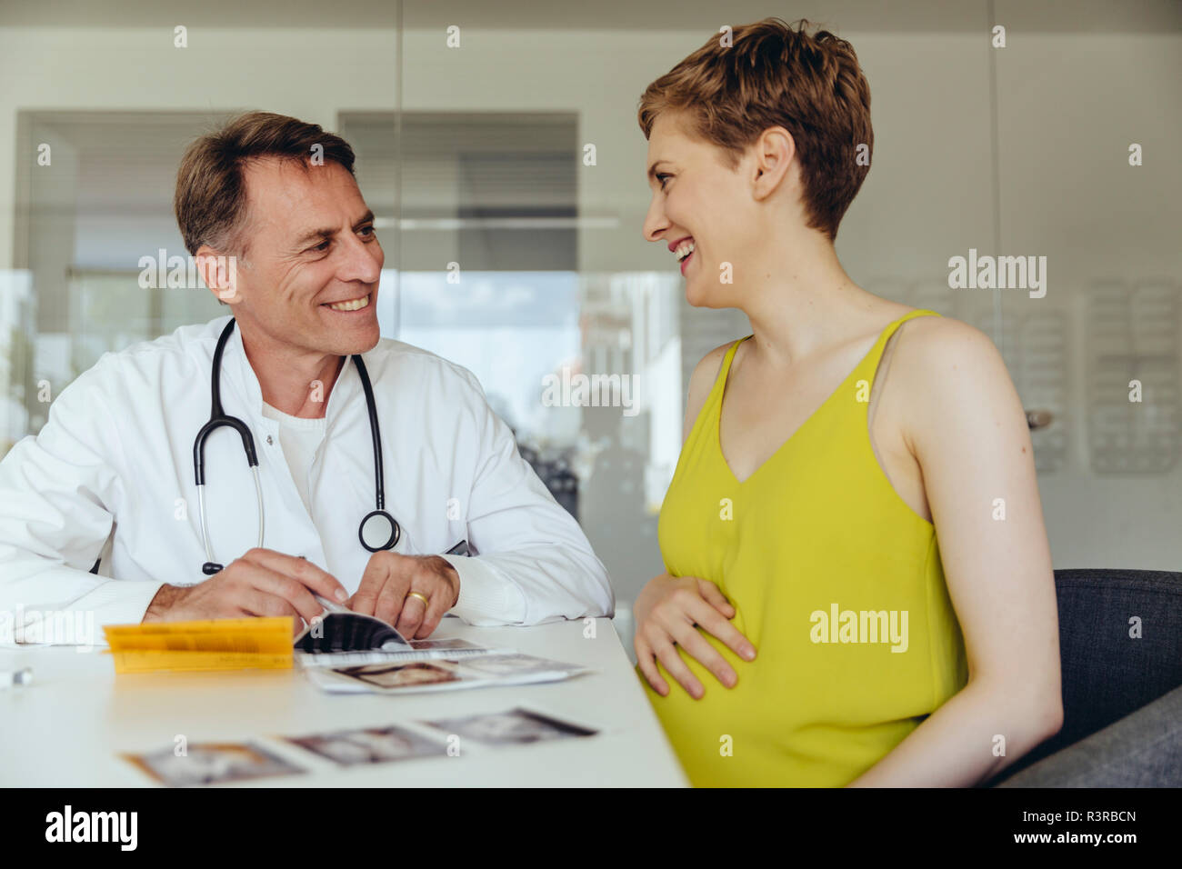 Pregnant woman discussing ultrasonic scans with her doctor - Stock Image