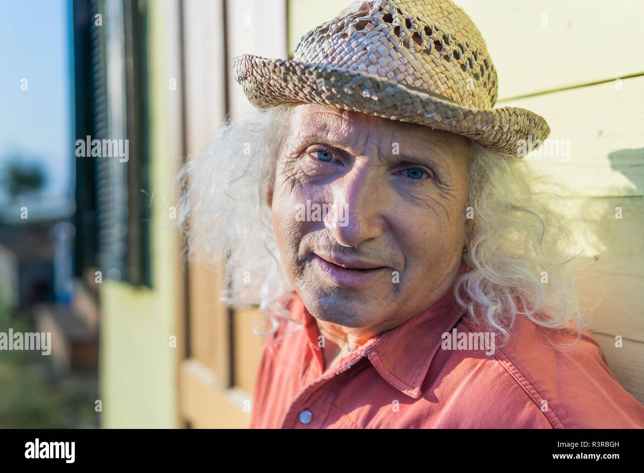 Portrait of senior man with long gray hair wearing straw hat - Stock Image