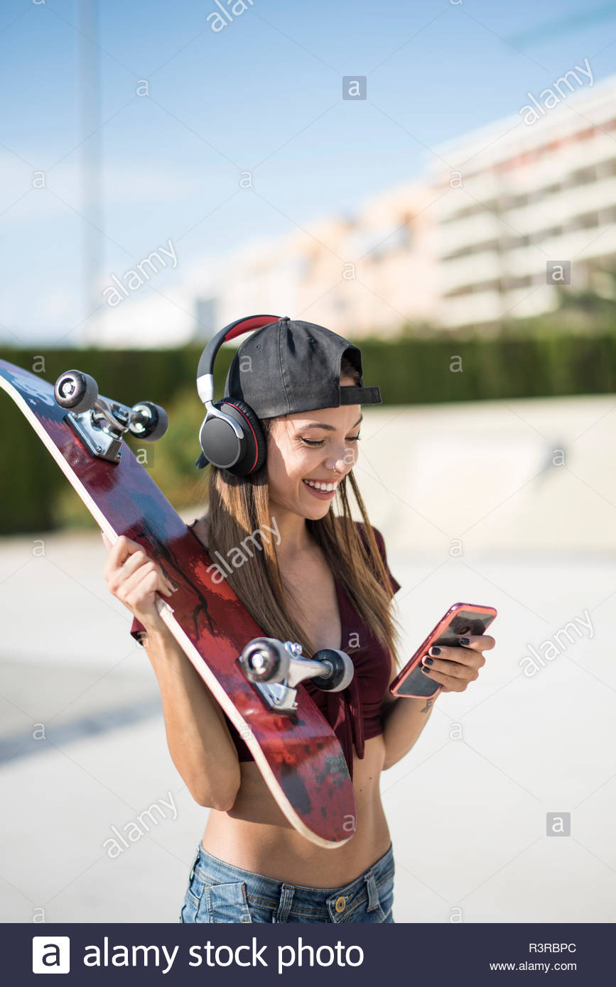 Young pretty woman in skatepark, listen music, using smartphone - Stock Image