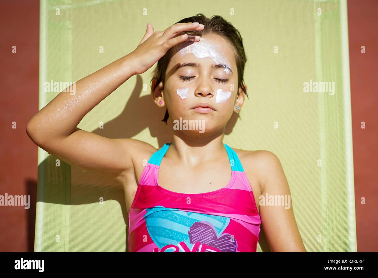 Young girl using suncream - Stock Image