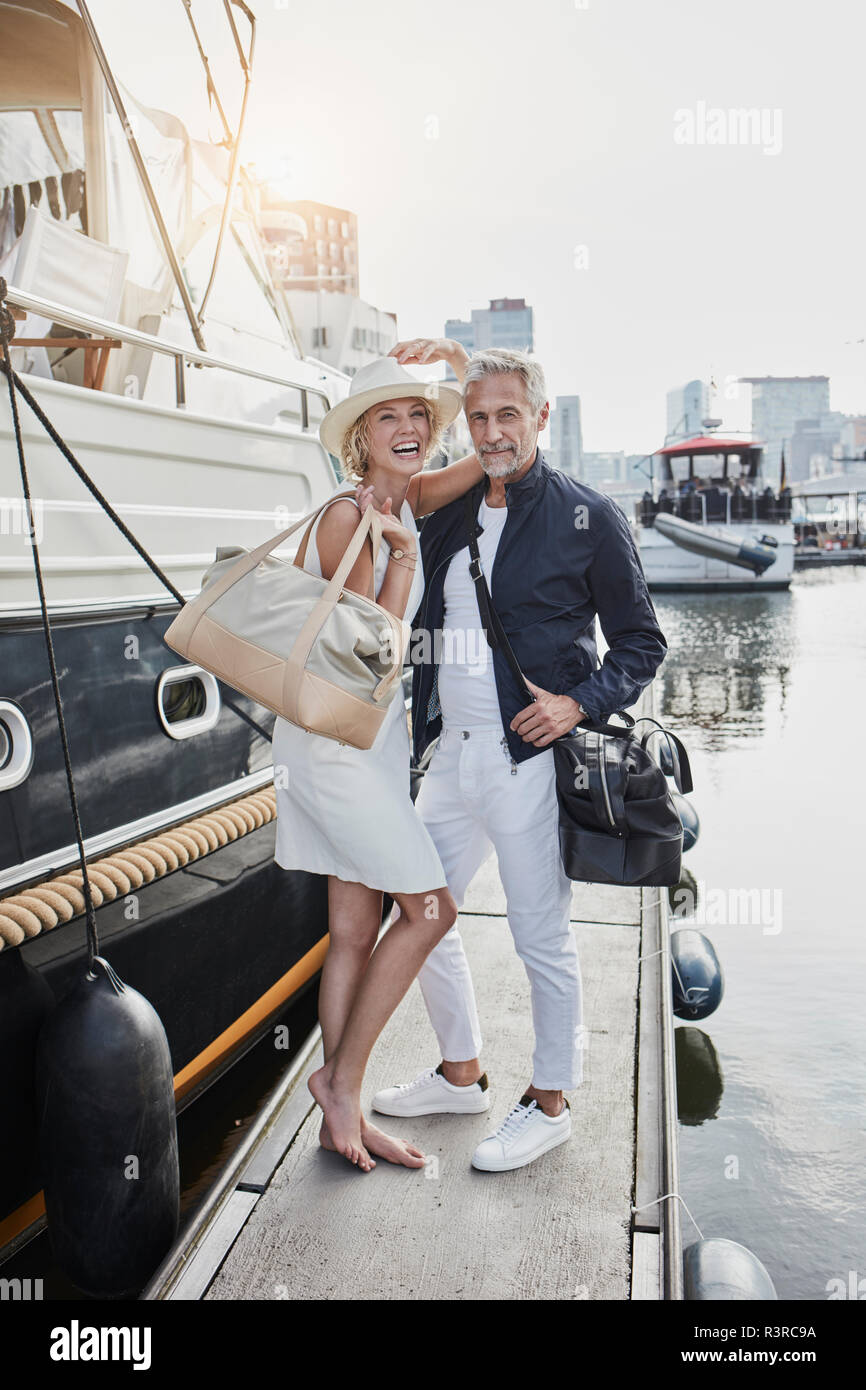 Older man and young woman standing with travelling bags on jetty next to yacht Stock Photo