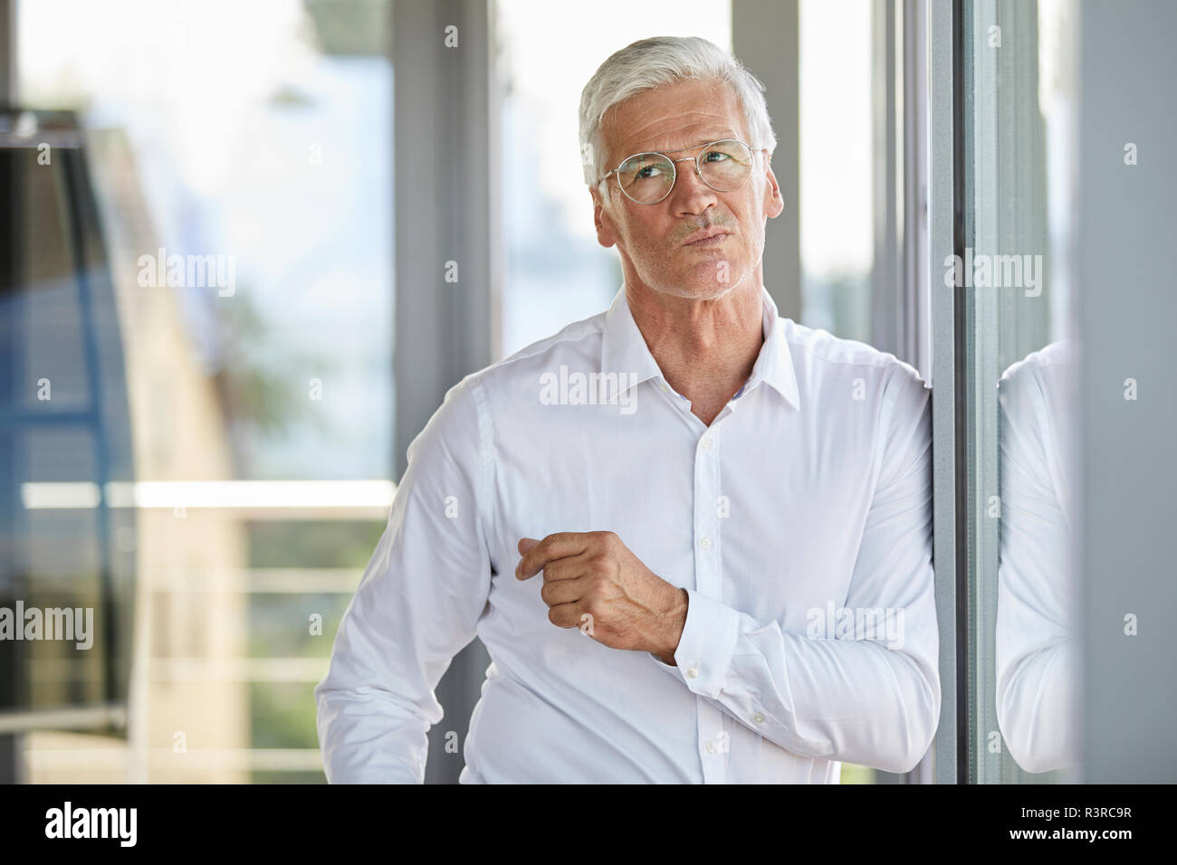 Businessman standing by window, contemplating - Stock Image