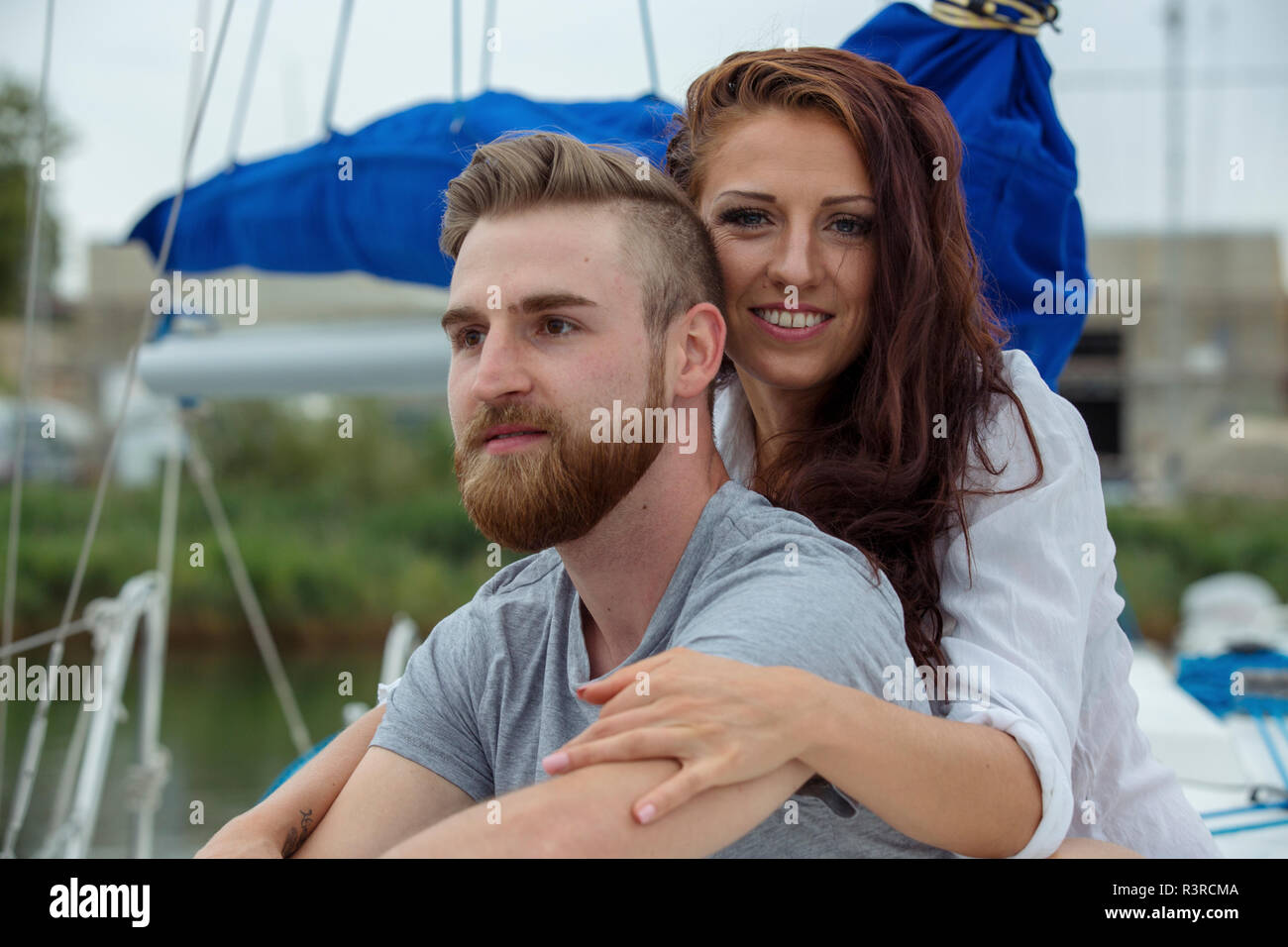 Portrait of a happy couple on a sailing boat - Stock Image