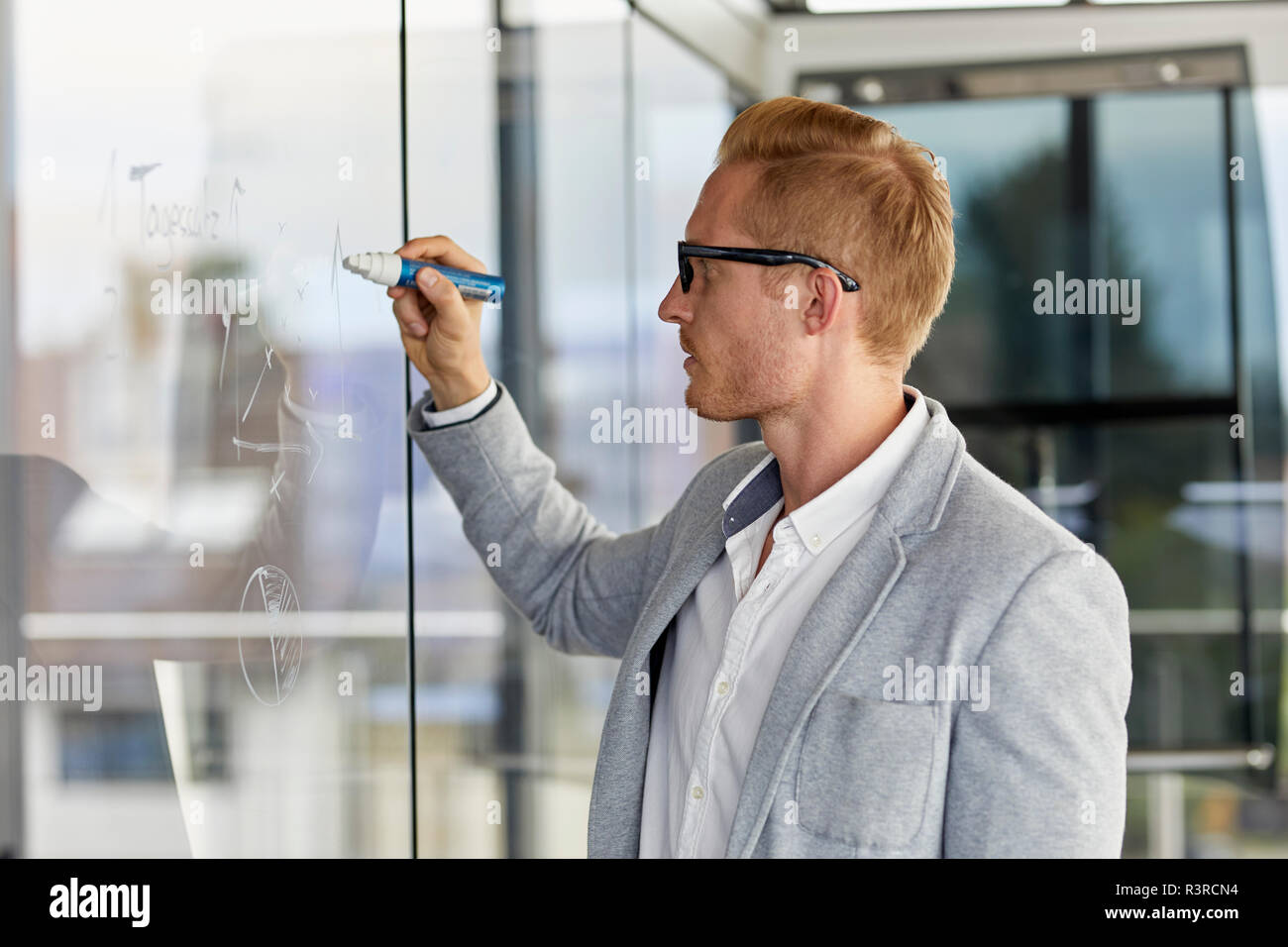 Businessman writing on glass pane in office - Stock Image
