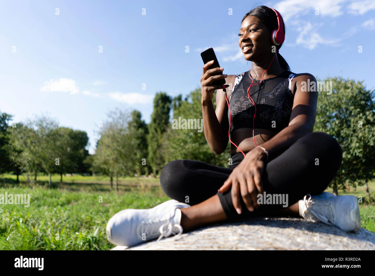 Young athlete sitting on straw bale, listening music with smartphone and headphones - Stock Image