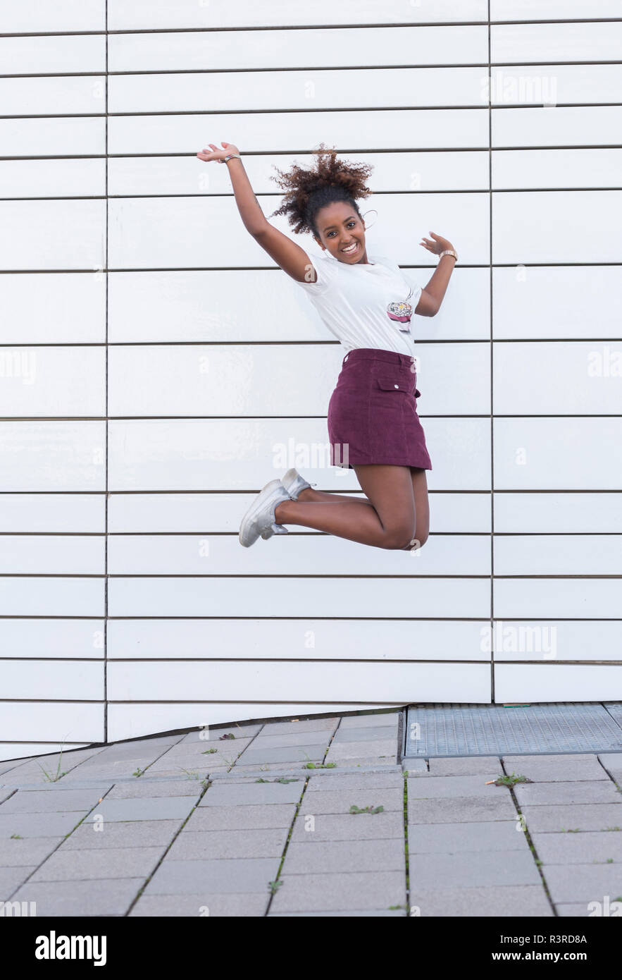 Portrait of laughing young woman jumping in the air - Stock Image