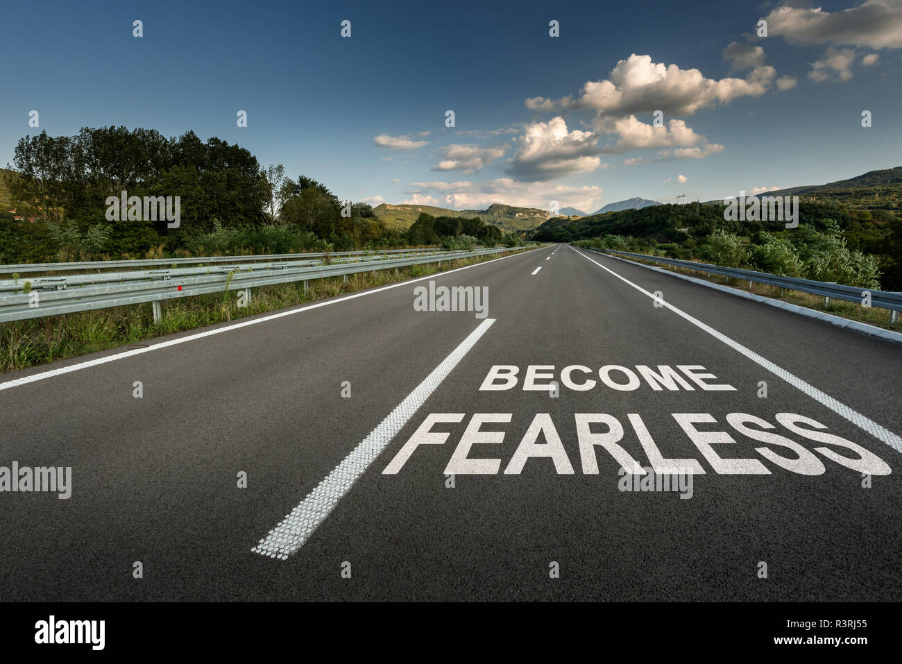 Become Fearless message on Asphalt highway road through the countryside to the mountains - Stock Image