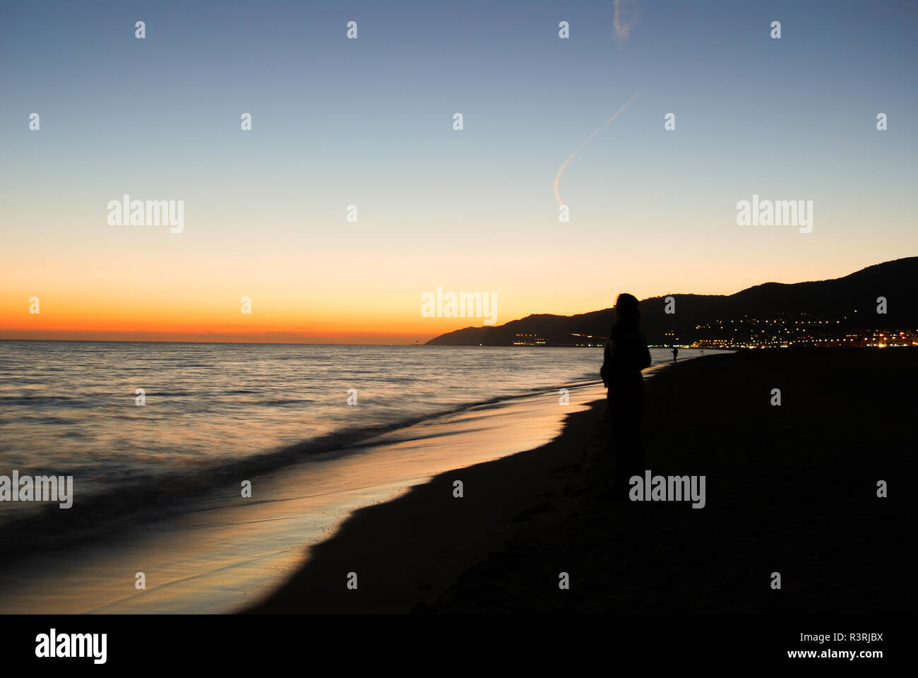 Photograph in beaches of Barcelona at dusk, with silhouette of woman on the shore. - Stock Image