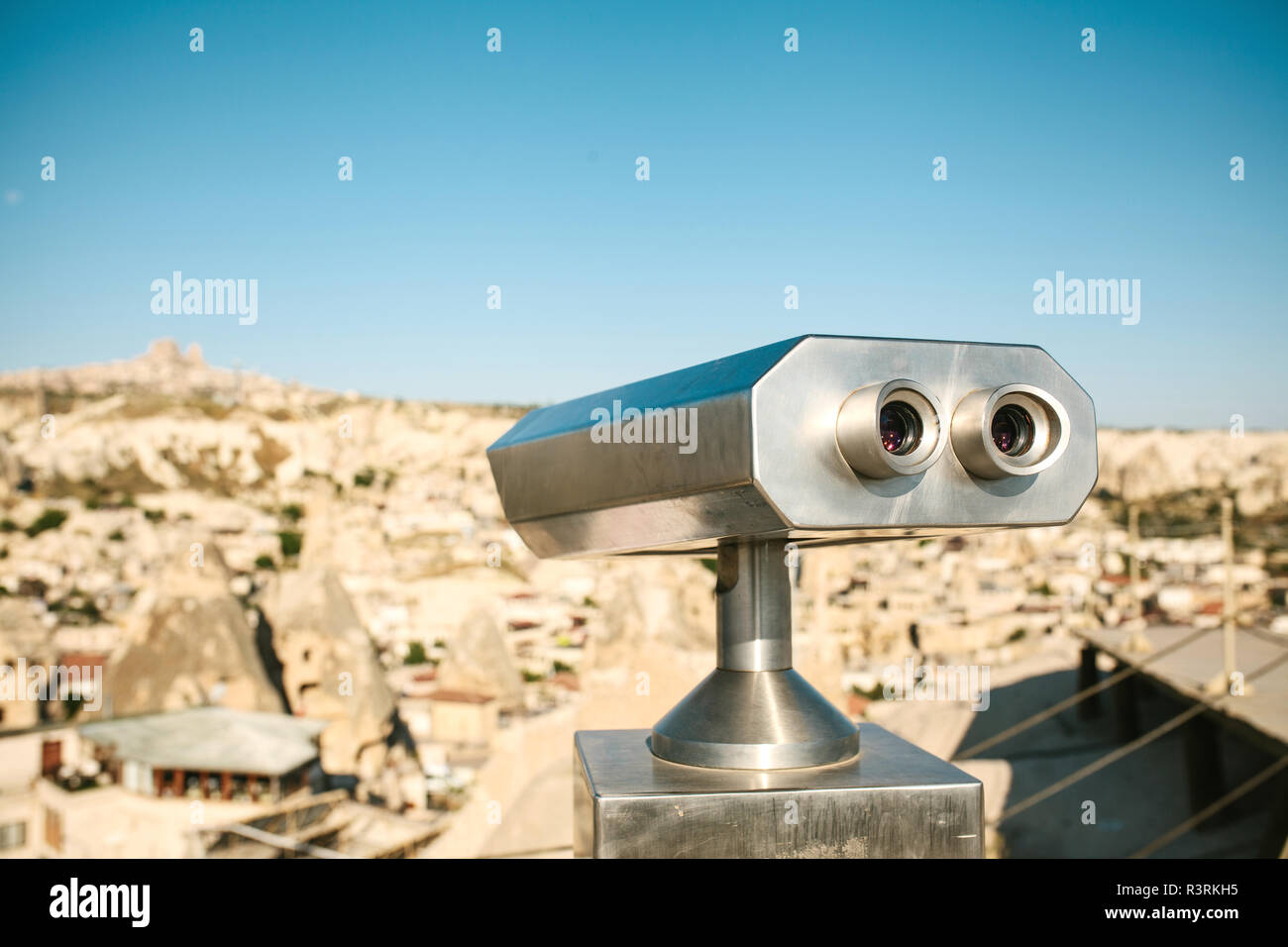Binoculars on the viewing platform. Ahead is a blurred view of a city called Goreme in Cappadocia in Turkey. Sightseeing. Stock Photo