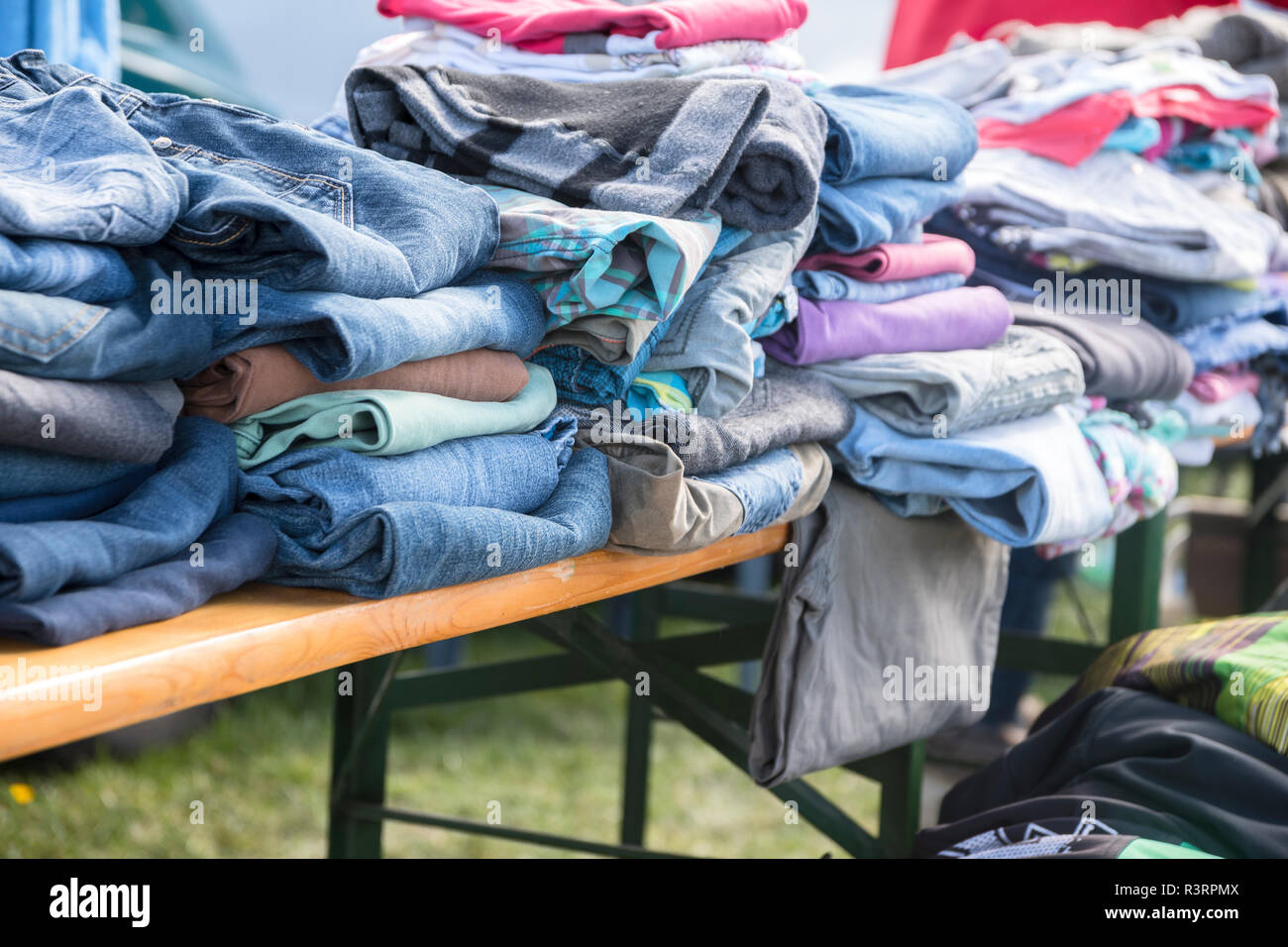 clothing collection like jeans, shirts and sweaters for the indigent or for sale at a flea market, selected focus, narrow depth of field - Stock Image